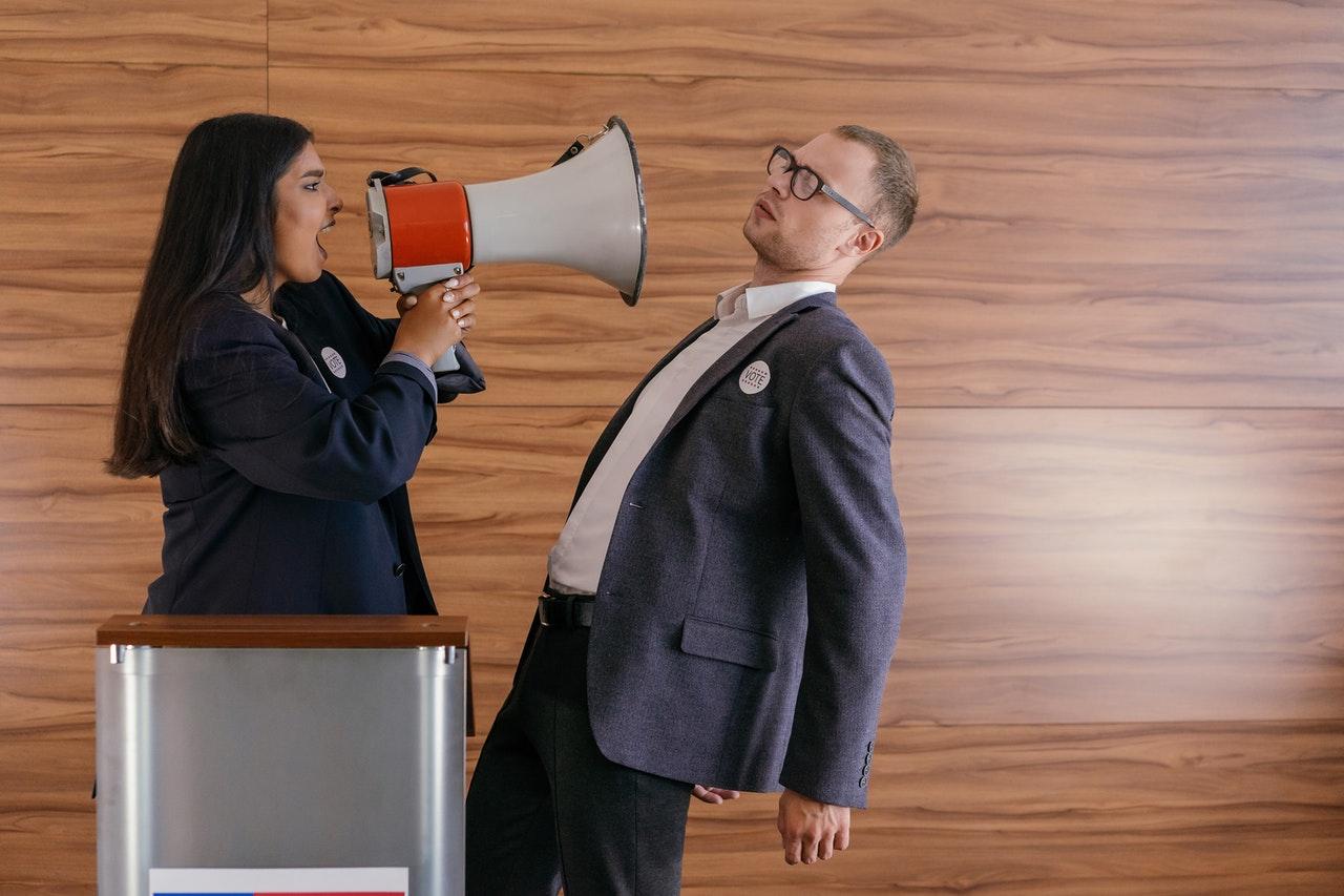Vor einer Holzwand steht eine Frau mit einem Lautsprecher, die einen Mann anschreit